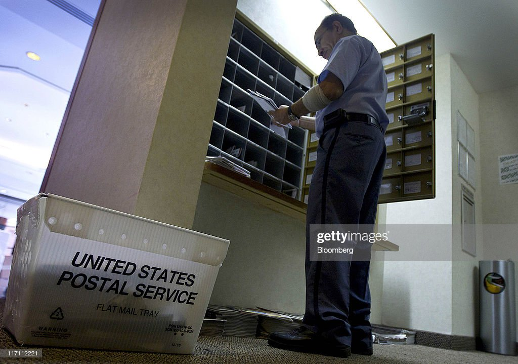 A U.S. Postal Service worker distributes letters to mailboxes in New York, U.S., on Wednesday, June 22, 2011. The U.S. Postal Service, facing insolvency without approval to delay a $5.5 billion payment for worker health benefits, will suspend contributions to an employee retirement account to save $800 million this year. Photographer: Jin Lee/Bloomberg via Getty Images