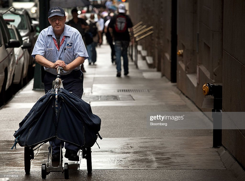 A U.S. Postal Service worker pushes a mail cart in New York, U.S., on Thursday, June 23, 2011. The U.S. Postal Service, facing insolvency without approval to delay a $5.5 billion payment for worker health benefits, will suspend contributions to an employee retirement account to save $800 million this year. Photographer: Timothy Fadek/Bloomberg via Getty Images