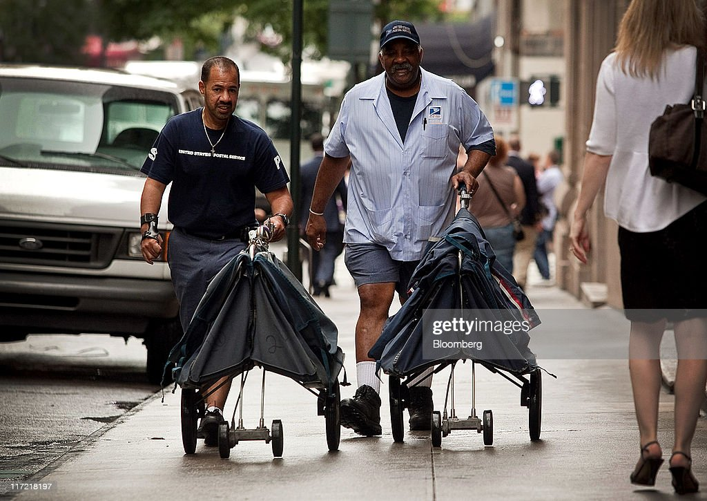 U.S. Postal Service workers push a mail carts in New York, U.S., on Thursday, June 23, 2011. The U.S. Postal Service, facing insolvency without approval to delay a $5.5 billion payment for worker health benefits, will suspend contributions to an employee retirement account to save $800 million this year. Photographer: Timothy Fadek/Bloomberg via Getty Images