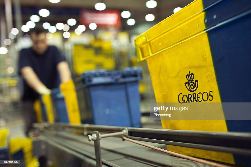 A postal worker arranges Correos-branded crates on a conveyor belt at the central sorting office of Sociedad Estatal Correos y Telegrafos SA, also known as Correos, in Madrid, Spain, on Tuesday, Jan. 15, 2013. Spain plans to privatize its state-owned postal company, Sociedad Estatal Correos y Telegrafos SA, Expansion reported citing Federico Ferrer, Vice Chairman of the state holding company. Photographer: Angel Navarrete/Bloomberg via Getty Images