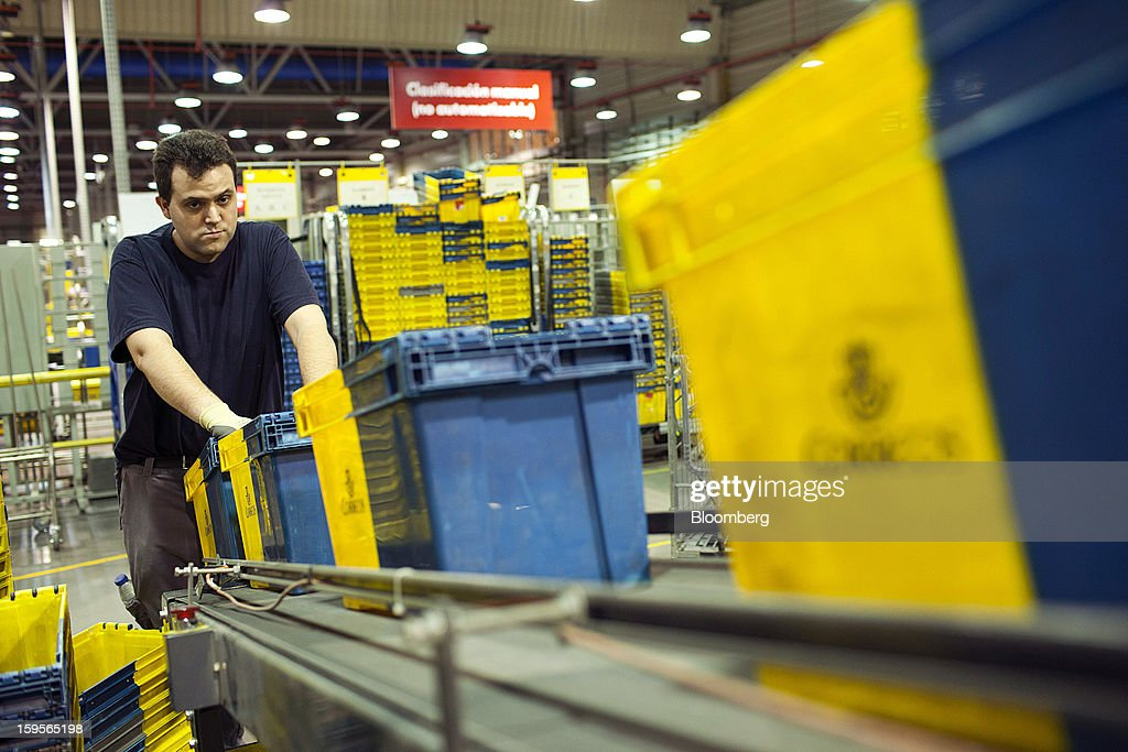A postal worker arranges crates on a conveyor belt at the central sorting office of Sociedad Estatal Correos y Telegrafos SA, also known as Correos, in Madrid, Spain, on Tuesday, Jan. 15, 2013. Spain plans to privatize its state-owned postal company, Sociedad Estatal Correos y Telegrafos SA, Expansion reported citing Federico Ferrer, Vice Chairman of the state holding company. Photographer: Angel Navarrete/Bloomberg via Getty Images
