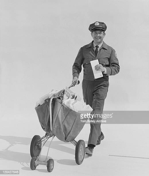 Postal worker carrying letters on wheel barrow against white background, portrait