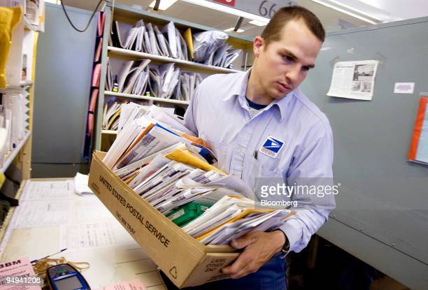 Postal worker Chris Ecker arranges his mail for delivery at the post office in Huntington Station New York US on Thursday April 16 2009 The USPS has...