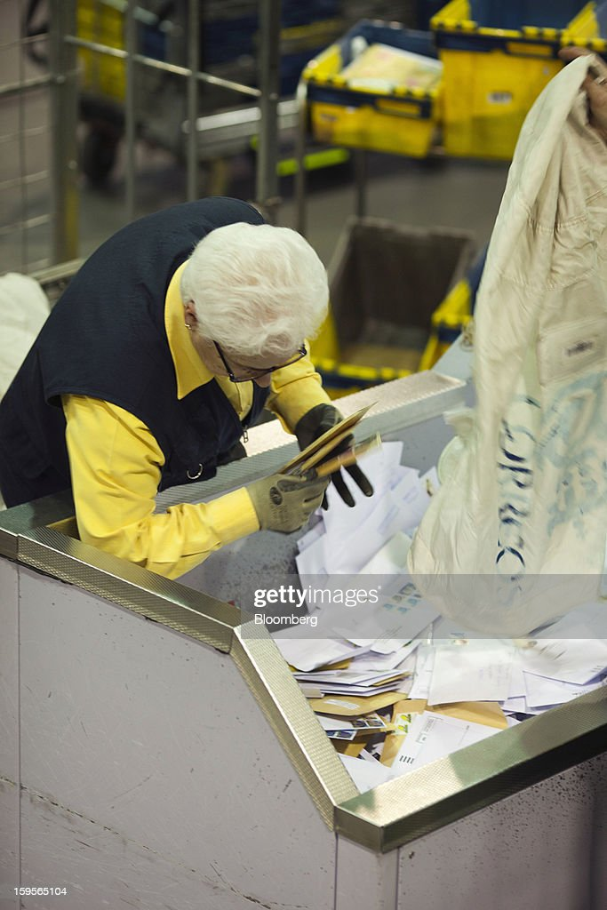 A postal worker collects letters from a sorting bin at the central sorting office of Sociedad Estatal Correos y Telegrafos SA, also known as Correos, in Madrid, Spain, on Tuesday, Jan. 15, 2013. Spain plans to privatize its state-owned postal company, Sociedad Estatal Correos y Telegrafos SA, Expansion reported citing Federico Ferrer, Vice Chairman of the state holding company. Photographer: Angel Navarrete/Bloomberg via Getty Images