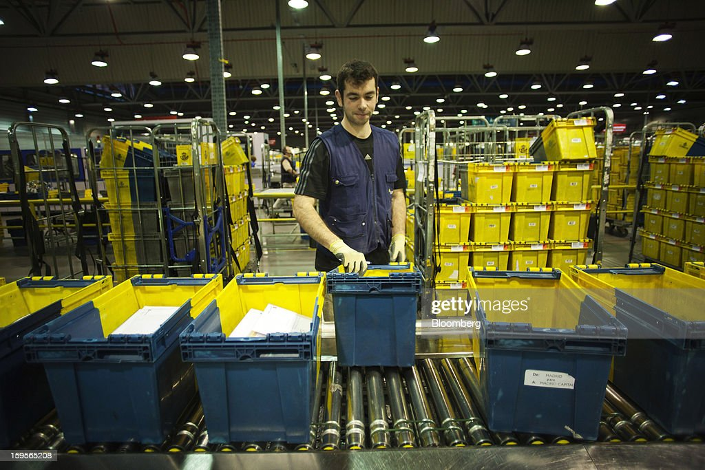A postal worker handles mail crates on conveyor rollers at the central sorting office of Sociedad Estatal Correos y Telegrafos SA, also known as Correos, in Madrid, Spain, on Tuesday, Jan. 15, 2013. Spain plans to privatize its state-owned postal company, Sociedad Estatal Correos y Telegrafos SA, Expansion reported citing Federico Ferrer, Vice Chairman of the state holding company. Photographer: Angel Navarrete/Bloomberg via Getty Images