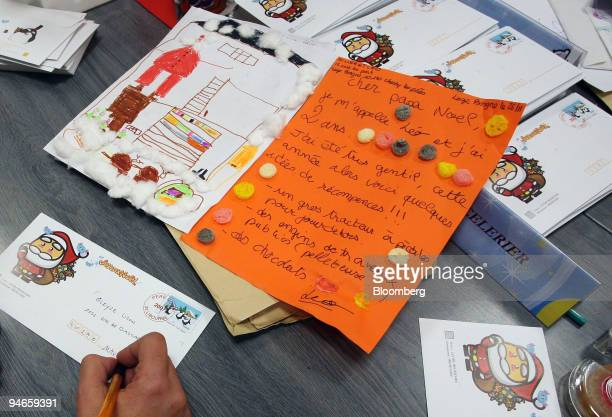 A postal worker replies to a letter addressed to Santa Claus at the La Poste office in Libourne in the Bordeaux region of France on Wednesday Nov 28...