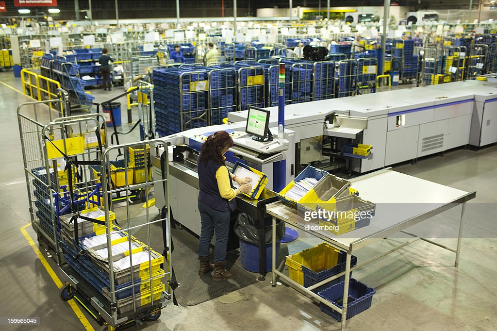 A postal worker sorts letters in mail crates at the central sorting office of Sociedad Estatal Correos y Telegrafos SA, also known as Correos, in Madrid, Spain, on Tuesday, Jan. 15, 2013. Spain plans to privatize its state-owned postal company, Sociedad Estatal Correos y Telegrafos SA, Expansion reported citing Federico Ferrer, Vice Chairman of the state holding company. Photographer: Angel Navarrete/Bloomberg via Getty Images