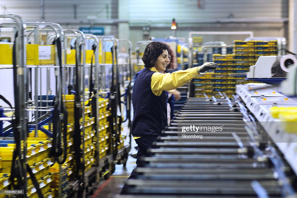 A postal worker sorts letters using an automatic sorting machine at the central sorting office of Sociedad Estatal Correos y Telegrafos SA, also known as Correos, in Madrid, Spain, on Tuesday, Jan. 15, 2013. Spain plans to privatize its state-owned postal company, Sociedad Estatal Correos y Telegrafos SA, Expansion reported citing Federico Ferrer, Vice Chairman of the state holding company. Photographer: Angel Navarrete/Bloomberg via Getty Images