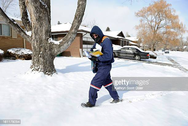 US Postal worker Tony Vallejos makes his way across the lawns of his mail customers after dressing carefully this morning for the frigid temperatures...