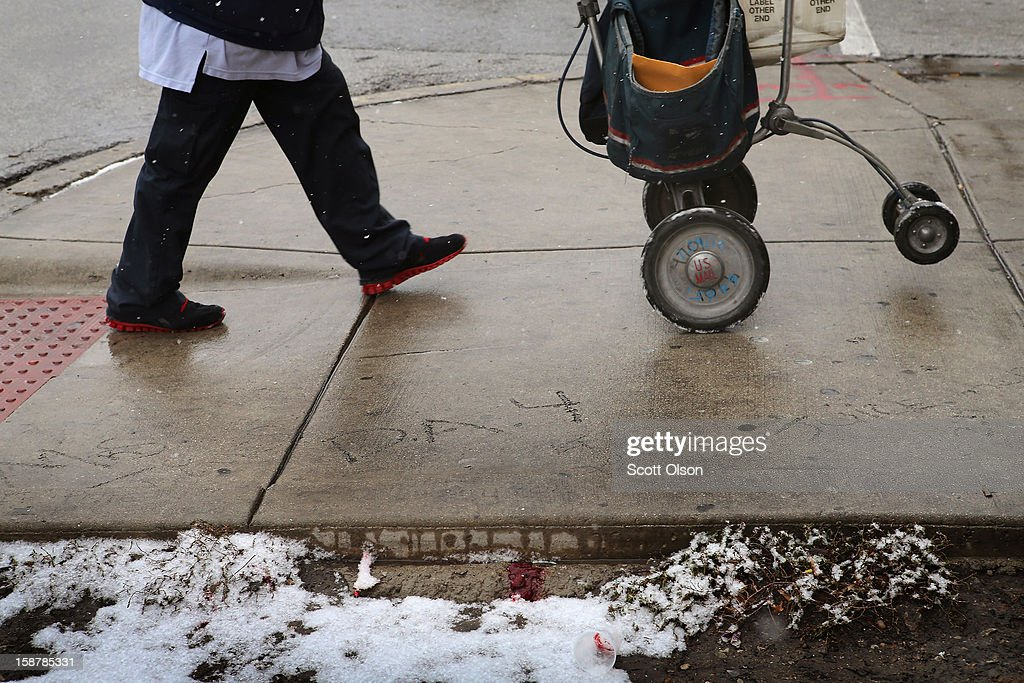 A postal worker walks past blood and tissue that remain on the ground outside Noah Foods neighborhood store on December 28, 2012 in Chicago, Illinois. Nathaniel Jackson, believed to be the 500th murder victim of the year in Chicago, was shot in the head and killed outside the store on December 27. After news organizations began reporting about his murder, the Chicago Police Department's News Affairs Office issued a statement stating Chicago's murder total remains at 499 because classification of one death investigation remains pending. They would not specify which death is pending. The total number of murders in the city has only once exceeded 500 victims since 2004. The murder rate is up about 11 percent from 2011, much of which is attributed to growing gang violence.