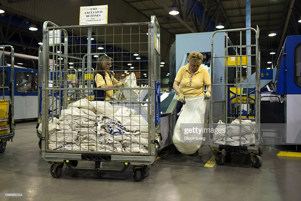 Postal workers empty mail sacks into a letter sorting machine at the central sorting office of Sociedad Estatal Correos y Telegrafos SA, also known as Correos, in Madrid, Spain, on Tuesday, Jan. 15, 2013. Spain plans to privatize its state-owned postal company, Sociedad Estatal Correos y Telegrafos SA, Expansion reported citing Federico Ferrer, Vice Chairman of the state holding company. Photographer: Angel Navarrete/Bloomberg via Getty Images
