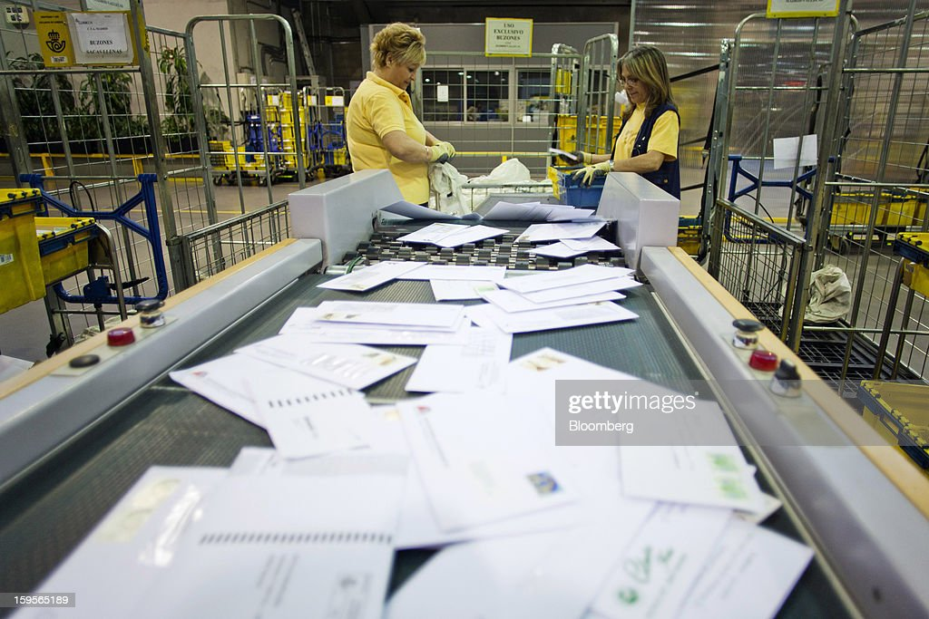Postal workers load letters onto a conveyor belt sorting machine at the central sorting office of Sociedad Estatal Correos y Telegrafos SA, also known as Correos, in Madrid, Spain, on Tuesday, Jan. 15, 2013. Spain plans to privatize its state-owned postal company, Sociedad Estatal Correos y Telegrafos SA, Expansion reported citing Federico Ferrer, Vice Chairman of the state holding company. Photographer: Angel Navarrete/Bloomberg via Getty Images