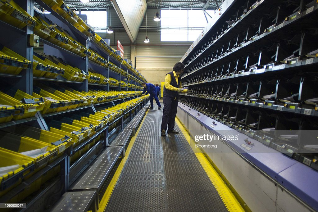 Postal workers sort letters in an aisle between automatic sorting machines at the central sorting office of Sociedad Estatal Correos y Telegrafos SA, also known as Correos, in Madrid, Spain, on Tuesday, Jan. 15, 2013. Spain plans to privatize its state-owned postal company, Sociedad Estatal Correos y Telegrafos SA, Expansion reported citing Federico Ferrer, Vice Chairman of the state holding company. Photographer: Angel Navarrete/Bloomberg via Getty Images