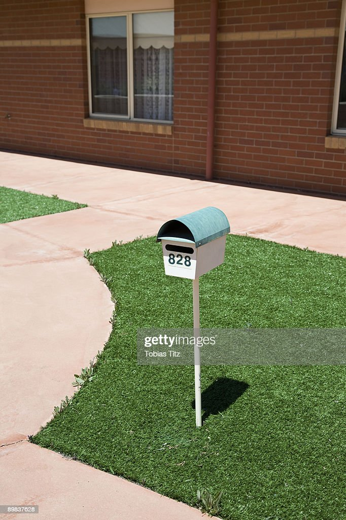 A postbox on a lawn outside of a house : Stock Photo