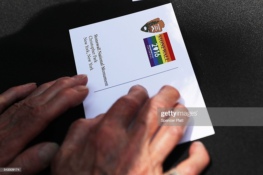 A postcard handed out by employees of the National Park Service with stamps commemorating the Stonewall Inn as a national monument is viewed at a dedication ceremony officially designating the Stonewall Inn as a national monument to gay rights on June 27, 2016 in New York City. Elected and federal officials joined members of the LGBT community at the dedication ceremony of the historic bar that has played a pivotal role in the battle for the rights of people in the gay community. White House Senior Advisor Valerie Jarrett, Director of the National Park Service Jonathan Jarvis, Mayor Bill de Blasio and others were all on hand for the afternoon ceremony.