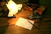 Postcard, ink, pen, lamp and stack of books