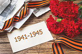 Postcard may 9 - red carnations Ribbon George Old photos on a wooden background. Symbol of victory in the great Patriotic war.