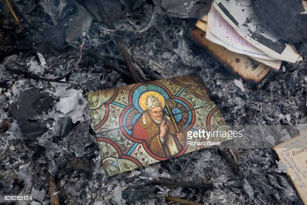 A postcard of patron Saint Nicholas all that is left after the burning on a bonfire of religious mementoes personal data accounts records and general...