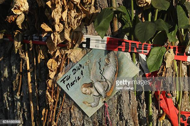 A postcard showing an angel that reads 'For you Maria' hangs among flowers left by mourners and police tape that adorn a tree near the spot where...
