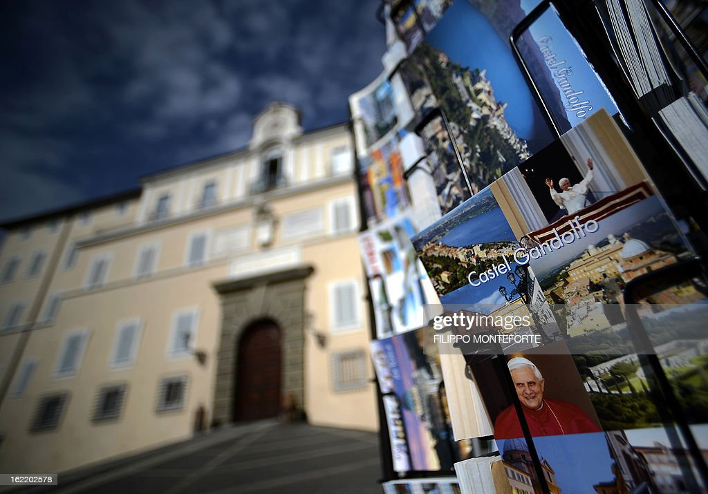 Postcards are displayed on February 20, 2013 outside a souvenirs shop by the Apostolic Palace on the main square of Castel Gandolfo, Italy. Pope Benedict XVI will stay at the Vatican's summer residence from February 28 until the convent of Mater Ecclesiae (Mother of the Church) at the Vatican will be ready to host him. Pope Benedict XVI began a week-long spiritual retreat out of the public eye on February 18 ahead of his resignation on February 28 with the field of candidates to succeed him still wide open. AFP PHOTO / FILIPPO MONTEFORTE