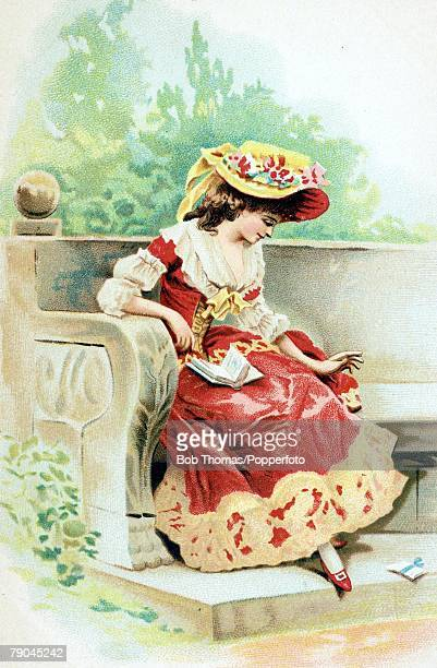Postcards Circa 1915 A colour illustration of a lady wearing a smart red coloured fashionable dress whilst sitting in a garden