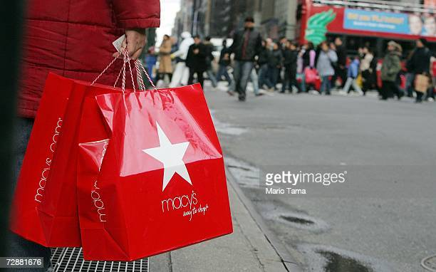 A postChristmas shopper holds Macy's bags as other shoppers cross Seventh Avenue December 27 2006 in New York City Retailers are hoping that...