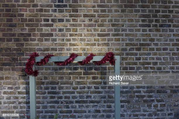 PostChristmas tinsel wrapped around a rail on 2nd January 2017 at a lock on Regent's Canal central London England