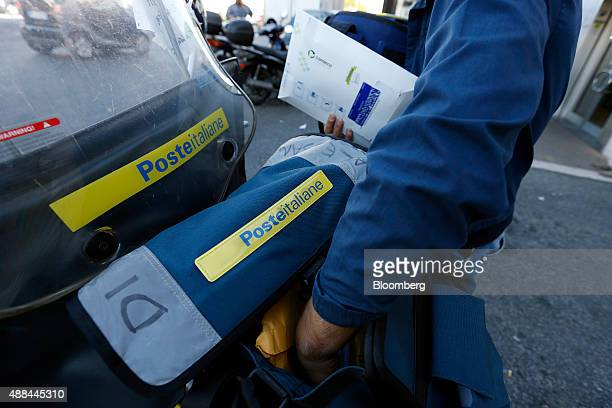 A Poste Italiane SpA postman takes mail from a bag on his scooter as he delivers mail in Rome Italy on Thursday Sept 10 2015 Italy is proceeding with...