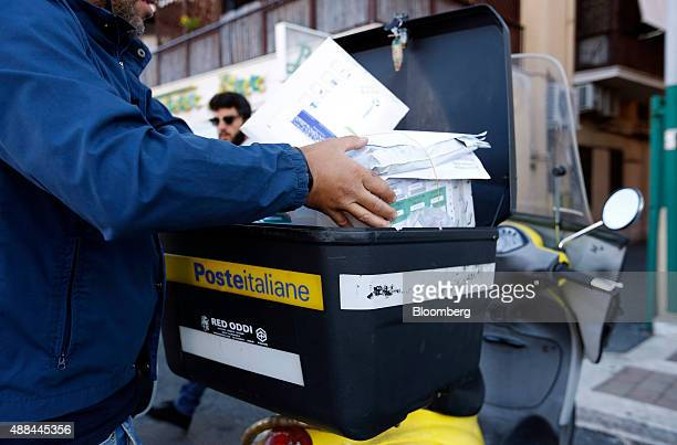 A Poste Italiane SpA postman takes mail from a box on his scooter in Rome Italy on Thursday Sept 10 2015 Italy is proceeding with a plan to sell as...