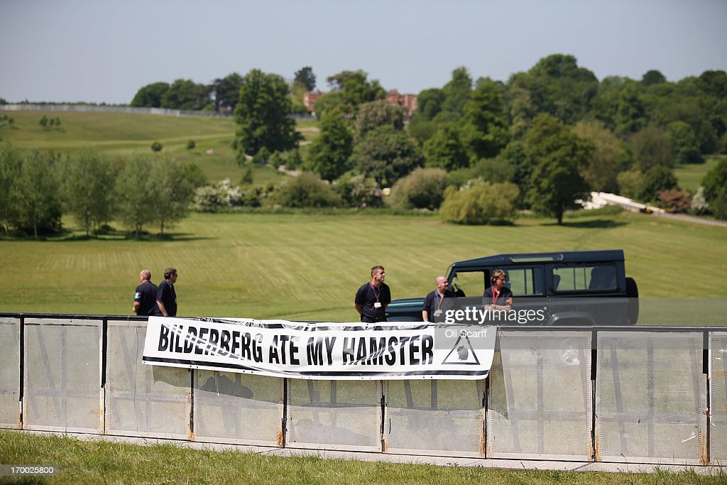 A poster adorns the security barrier of the protester encampment outside The Grove hotel, which is hosting the annual Bilderberg conference, on June 6, 2013 in Watford, England. The traditionally secretive conference, which has taken place since 1954, is expected to be attended by politicians, bank bosses, businessman and European royalty.