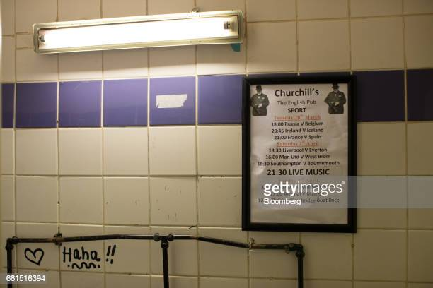 A poster advertising live sport including English Premier League soccer matches stands on the wall inside the toilets at Churchill's traditional...