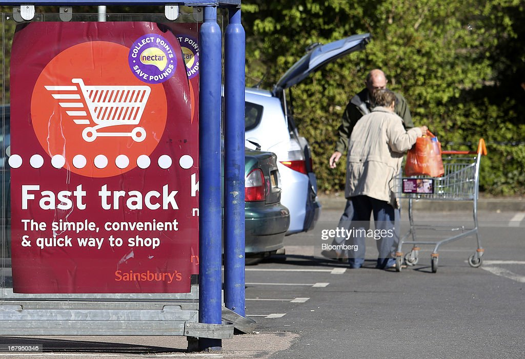 A poster advertising Sainsbury's Fast Track service is seen as customers load goods in to the trunk of an automobile after shopping at a Sainsbury's supermarket store, operated by J Sainsbury Plc, in Godalming, U.K., on Thursday, May 2, 2013. J Sainsbury Plc, the U.K.'s third-largest supermarket chain, will report full year results on May 8. Photographer: Chris Ratcliffe/Bloomberg via Getty Images