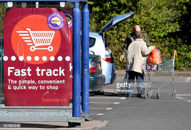 A poster advertising Sainsbury's Fast Track service is seen as customers load goods in to the trunk of an automobile after shopping at a Sainsbury's...