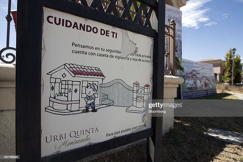A poster advising residents of security features hangs at the entrance gate to the Urbi Desarrollos Urbanos SAB's Urbi Quinta Montecarlo housing development in Cuautitlan Izcalli, Mexico, on Monday, Feb. 25, 2013. Urbi Desarrollos Urbanos SAB, the Mexican homebuilder that lost three-fourths of its market value in the past year, will report negative free cash flow to equity for the fourth quarter of 2012, according to a company official with direct knowledge of the matter. Photographer: Susana Gonzalez/Bloomberg via Getty Images