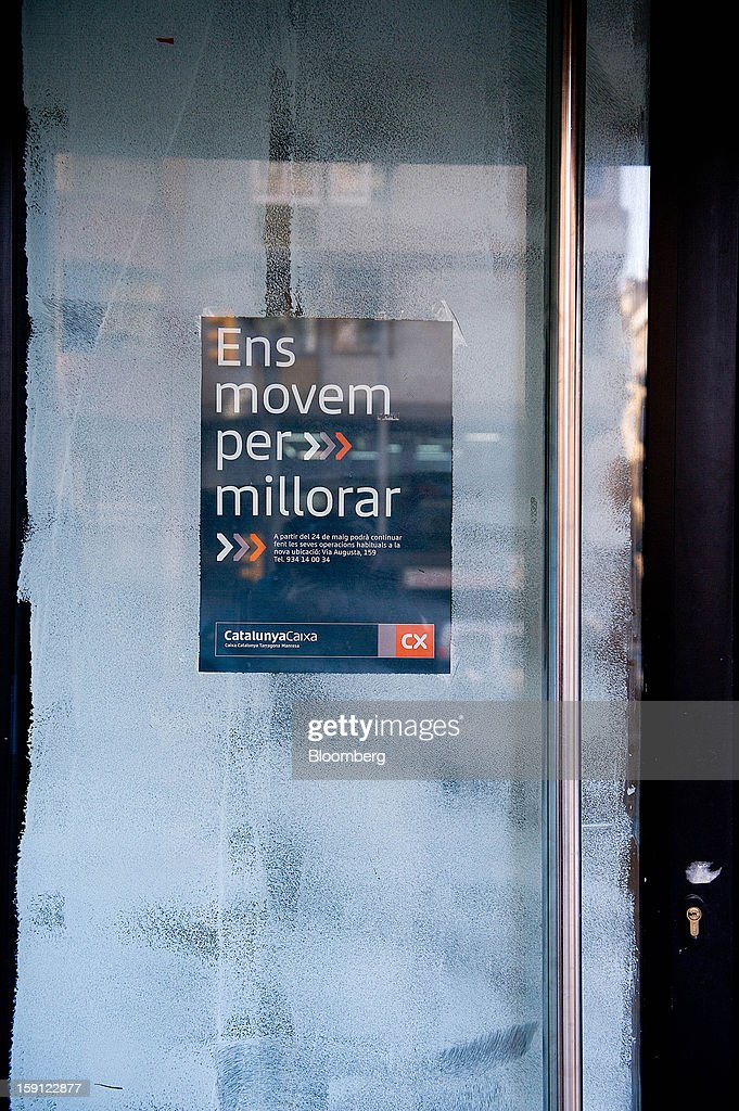 A poster announcing the closure of a CatalunyaCaixa bank branch sits on the office doors in Barcelona, Spain, on Tuesday, Jan. 8, 2013. Banco Santander SA, Spain's biggest lender, will offer 263 million euros ($345 million) in stock to buy out minority investors in its Banco Espanol de Credito SA retail unit and close 700 local branches to cut costs. Photographer: David Ramos/Bloomberg via Getty Images