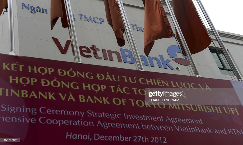 A poster announcing the investment agreement signing with Japanese bank Mitsubishi UFJ hangs in front of the main office building of the local commercial bank VietinBank is pictured in downtown Hanoi on December 27, 2012. Japan's biggest bank Mitsubishi UFJ on December 27 bought a 20 percent stake worth 743 million USD in state-owned VietinBank, the largest-ever foreign investment in Vietnam's banking sector. AFP PHOTO/HOANG DINH Nam