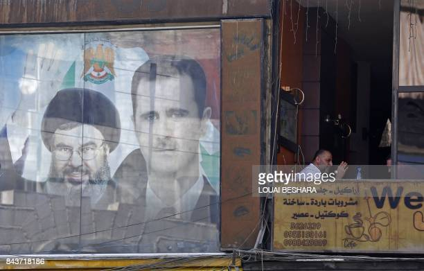 A poster bearing an image of Syrian President Bashar alAssad and Hassan Nasrallah head of Lebanese Shiite movement Hezbollah is seen in Damascus on...