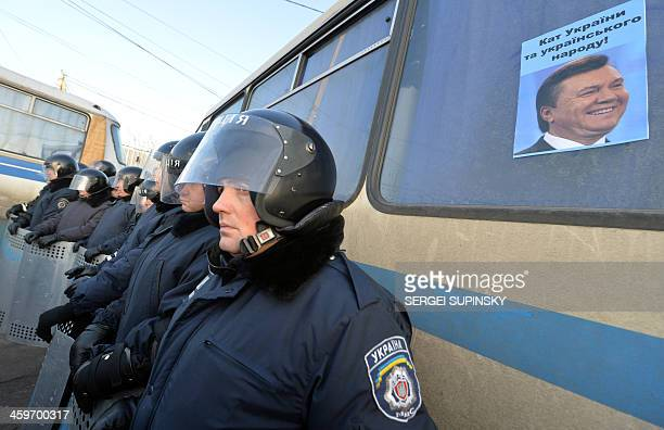 A poster depicting the President Viktor Yanukovych and signed 'Executioner of Ukrainian people' is stuck on a bus sriot policemen surrounded the...