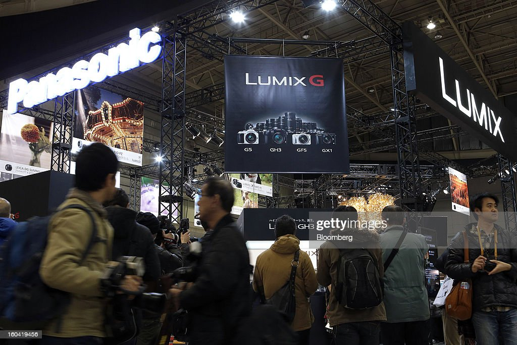A poster displaying Panasonic Corp. range of Lumix camera bodies and lenses hangs above visitors at the company's booth during the CP+ Camera and Photo Imaging Show in Yokohama City, Japan, on Thursday, Jan. 31, 2013. The CP+ Camera and Photo Imaging Show runs from Jan. 31 to Feb. 3. Photographer: Kiyoshi Ota/Bloomberg via Getty Images