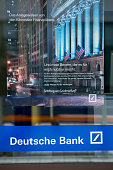 A poster featuring a photograph of the New York Stock Exchange sits in the window of Deutsche Bank AG branch in Boblingen Germany on Monday July 25...