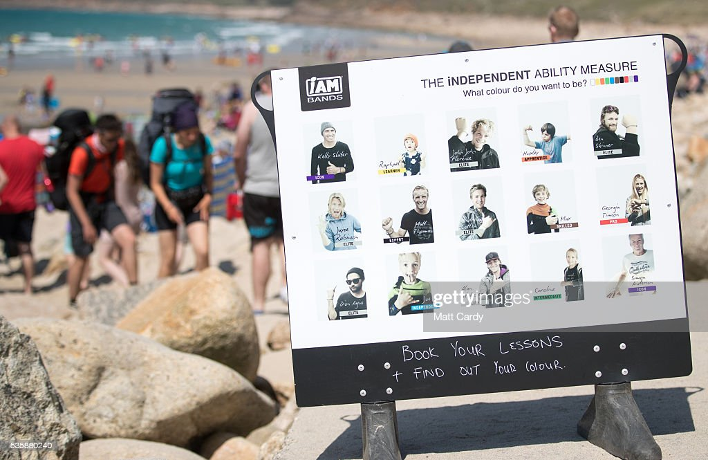 A poster for a surf school is seen as people swim and surf in the sea as they enjoy the fine weather at Sennen Cove on May 30, 2016 in Cornwall, England. As some parts of the UK were bathed in sunshine for the bank holiday weather forecasters have warned that gale-force winds and thunderstorms will sweep in from the east overnight.