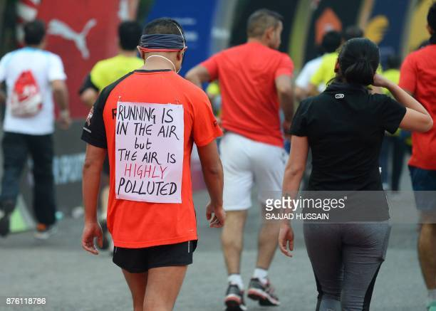 A poster is seen on the back of a man as he takes part in the Airtel Delhi Half Marathon 2017 in New Delhi on November 19 2017 / AFP PHOTO / SAJJAD...