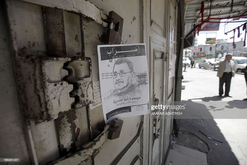 A poster of 63-year-old Palestinian prisoner Maisara Abu Hamdiyeh, who died of cancer at Soroka hospital in the southern Israeli city of Beersheva earlier in the week, hangs on the door of a closed shop in Nablus on April 3, 2013. The Palestinian territories held a general strike and day of mourning after a prisoner's death raised temperatures over the tinderbox issue of Palestinians in Israeli jails. AFP PHOTO/ JAAFAR ASHTIYEH