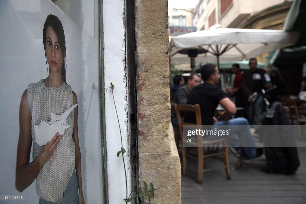 A poster of a woman holding a cut-out of Cyprus is seen next to a cafe in Faneromeni Square in Nicosia one day before the second run-off of the Cypriot presidential elections, on February 23, 2013. A second-round on February 24, being closely watched in European capitals pits right-wing opposition leader Nicos Anastasiades against Stavros Malas, who is backed by the communist party in power during the economic downturn, Akel.