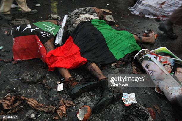 A poster of assassinated former Prime Minister Benazir Bhutto lies next to bomb blast victims covered in flags of Bhutto's Pakistan People's Party on...