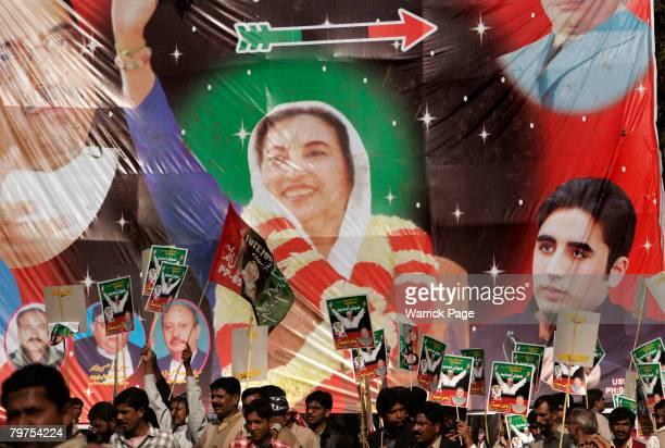A poster of Benazir Bhutto and her son Bilawal Bhutto Zardari is seen in the background as PPP supporters gather at an election rally February 14...