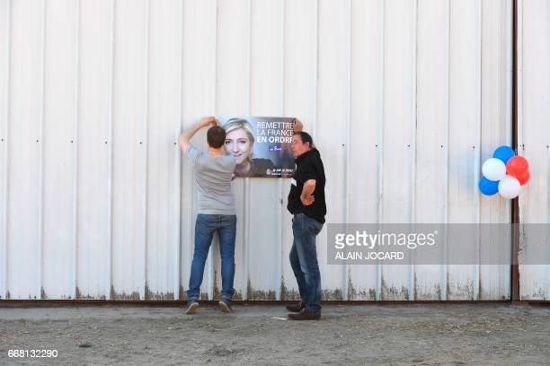 A poster of French presidential election candidate for the farright Front National party Marine Le Pen is hung on the door of a barn as the farm yard...