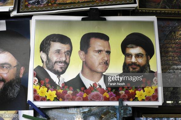 A poster of Hezbollah leader Sheik Hassan Nasrallah Syrian President Bashar AlAssad and Iranian President Mahmoud Ahmadinejad hangs for sale on the...