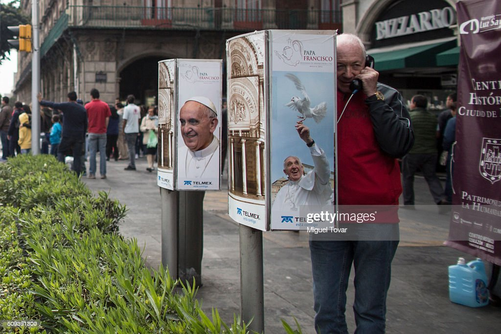 A poster of Pope Francis is displayed on a phone booths where a man uses a public phone at Zocalo Main Square on February 10, 2016 in Mexico City, Mexico. The Zocalo main square is closed to public, as the perimeter is prepared for the upcoming visit of Pope Francis on February 12-17.