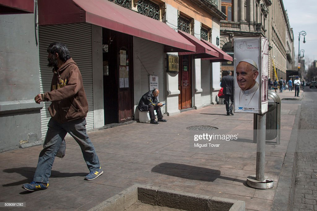 A poster of Pope Francis is seen on the side of a phone booth as people walk at Zocalo Main Square on February 10, 2016 in Mexico City, Mexico. The Zocalo main square is closed to public, as the perimeter is prepared for the upcoming visit of Pope Francis on February 12-17.